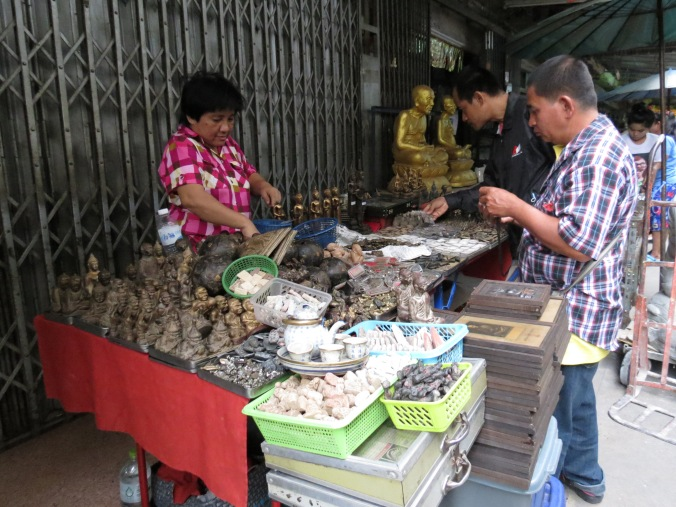 A Thai woman offers an assortment of amulets and trinkets for good fortune or whatnot.